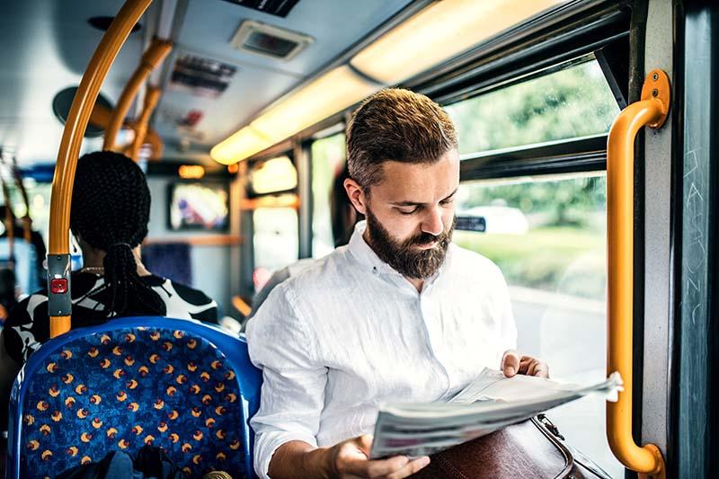 Mann liest im Bus eine Zeitung